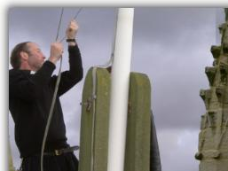 Rev Ian Wallis hoists the Feast flag - Click to Enlarge